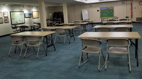 Room image showing a series of rectangular tables laid out classroom-style with circular tables to the left