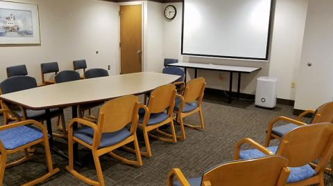 Room image showing conference table with seating on all sides, large projection screen, and additional chairs lining the walls