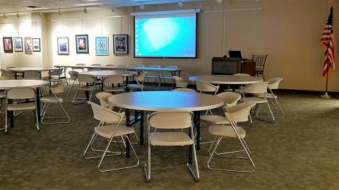 Waugaman Gallery complete with circular tables with seating at each table, projector and projection screen, lectern and rectangular table with seating
